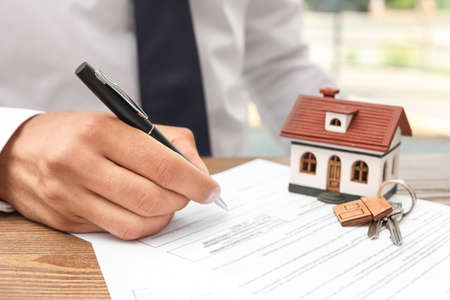 Man signing document at table in real estate agents office