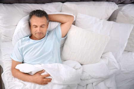 Homme dormant sur un oreiller confortable au lit à la maison, vue de dessus