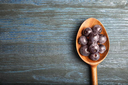 Spoon with fresh acai berries on wooden table, top view
