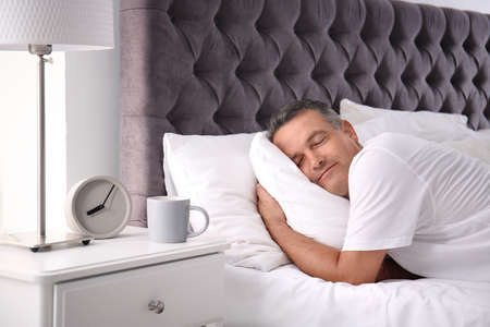 Man sleeping on comfortable pillow in bed at home Stock fotó