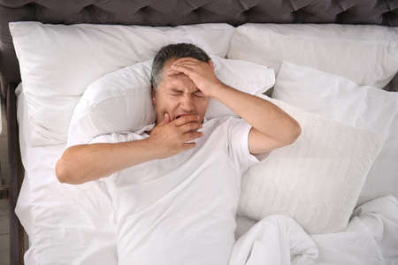 Man yawning after sleeping on comfortable pillow in bed at home Zdjęcie Seryjne