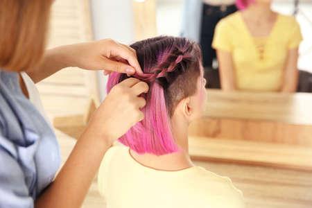 Professional stylist braiding woman's color hair in beauty salon. Modern trend