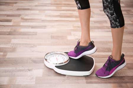 Vrouw haar gewicht meten met behulp van schalen op de vloer