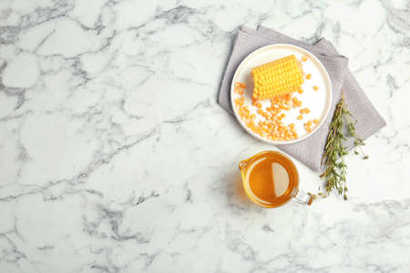 Flat lay composition with corn and jug of oil on marble background