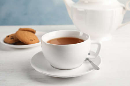 Cup of delicious tea with saucer on table