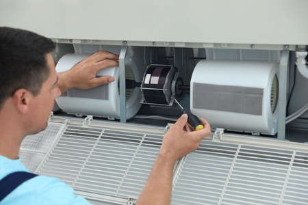 Technician repairing and checking air conditioner indoors