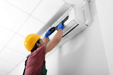 Técnico masculino control de aire acondicionado en interiores Foto de archivo