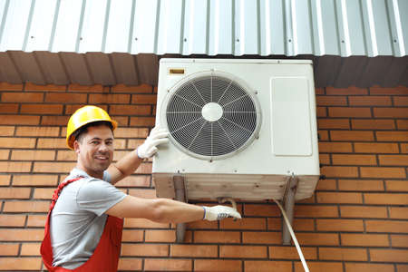 Male technician fixing air conditioner outdoors 版權商用圖片