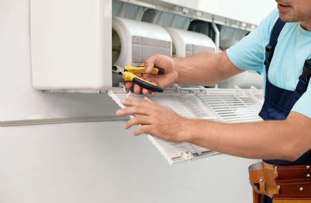 Male technician repairing modern air conditioner indoors