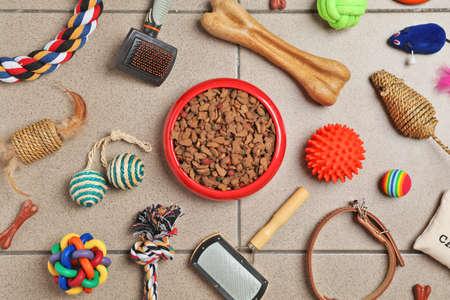 Ciotola con cibo per cane o gatto e accessori sul pavimento. Cura degli animali
