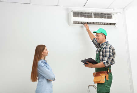 Male technician speaking with woman about air conditioner indoors