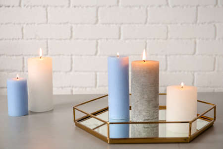 Tray with decorative candles on table against brick wall