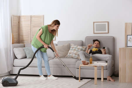 Lazy husband lying on sofa and his wife cleaning at home Stockfoto