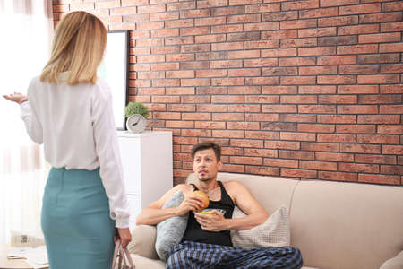 Lazy husband quarrelling with hardworking wife at home