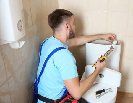 Professional plumber in uniform repairing toilet tank indoors
