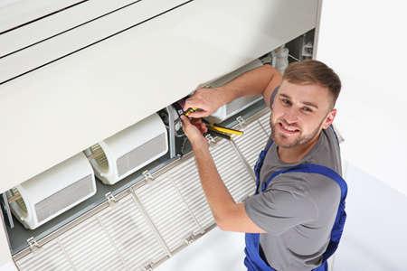 Macho joven técnico reparando aire acondicionado en interiores