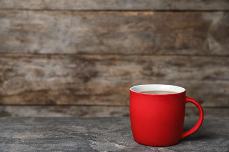 Red ceramic cup with hot aromatic coffee on table