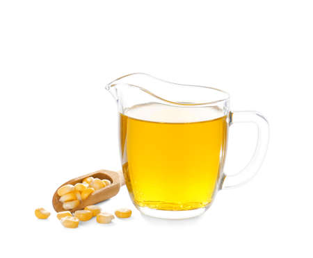 Jug with fresh corn oil and kernels on white background