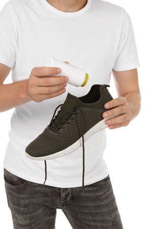 Man putting powder freshener into shoe on white background