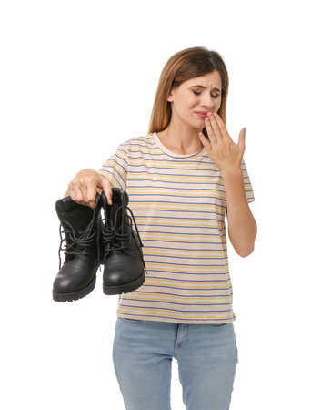 Woman feeling bad smell from shoes on white background. Air freshener
