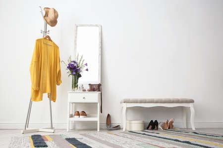 Stylish hallway interior with mirror and rack Stock Photo
