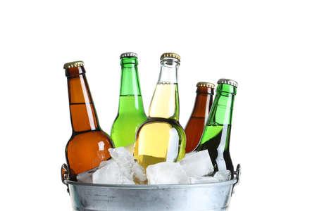 Botellas con diferentes tipos de cerveza y hielo en un cubo de metal sobre fondo blanco.