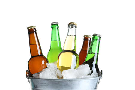 Bottles with different types of beer and ice in metal bucket on white background