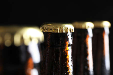 Many bottles of beer on dark background, closeup view
