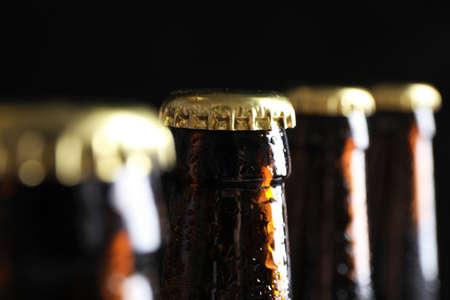 Muchas botellas de cerveza sobre fondo oscuro, vista de cerca