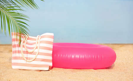 Colorful inflatable ring and bag on sand. Beach object Banco de Imagens