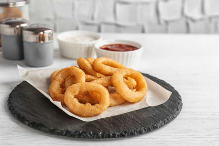 Slate plate with tasty onion rings on table Stock Photo