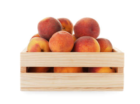Crate with fresh sweet peaches on white background