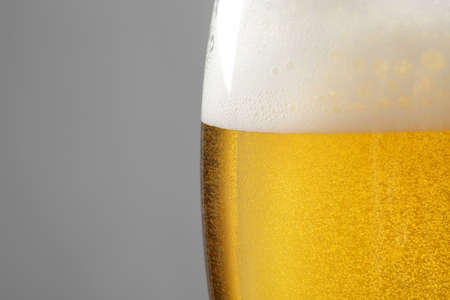Glass of tasty beer with foam on color background, closeup Stok Fotoğraf