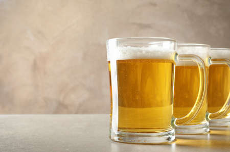 Glass mugs of cold tasty beer on table Banque d'images