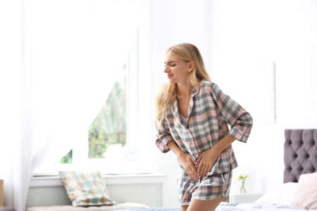 Young woman suffering from pain in bedroom. Gynecology concept Stock Photo