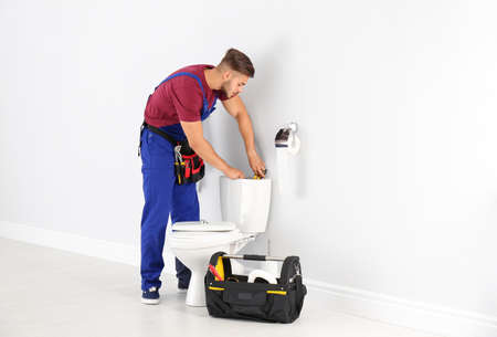 Young man working with toilet tank in bathroom Banque d'images
