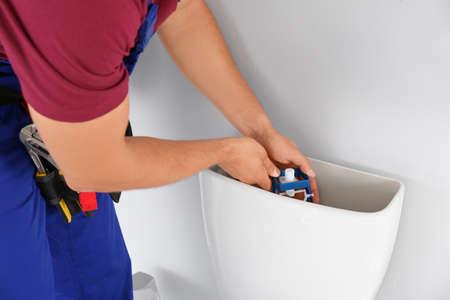Young man working with toilet tank in bathroom, closeup Foto de archivo