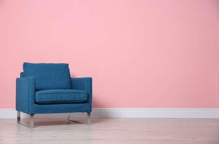 Comfortable armchair near color wall. Modern interior element