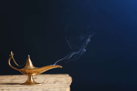 Aladdin Lampe der Wünsche auf Holztisch gegen dunklen Hintergrund