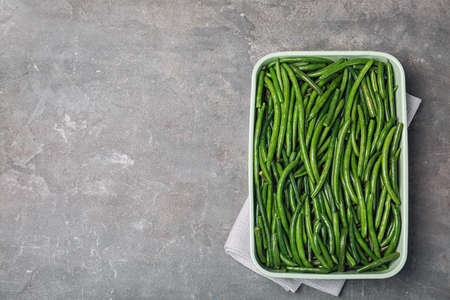 Dish with tasty green beans on table, top view
