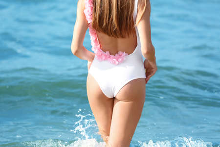 Attractive young woman in beautiful one-piece swimsuit on beach, closeup