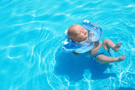 Cute little baby with inflatable neck ring in swimming pool on sunny day, outdoors