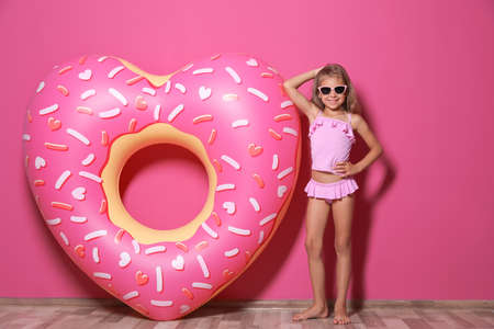 Cute little girl with bright heart shaped inflatable ring near color wall Stock Photo