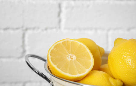 Colander with ripe lemons against brick wall