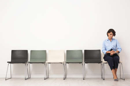 Young woman sitting on chair and waiting for job interview
