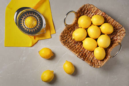 Flat lay composition with ripe lemons and juicer on gray table Stock Photo