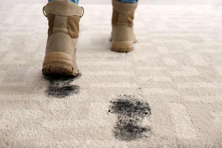 Person in dirty shoes leaving muddy footprints on carpet Standard-Bild