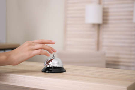 Woman ringing service bell on reception desk in hotel, closeup
