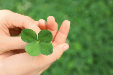 Woman holding four-leaf clover outdoors, closeup with space for text Stock Photo