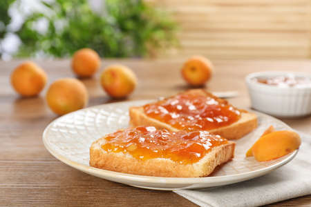 Bread with tasty apricot jam on plate Archivio Fotografico